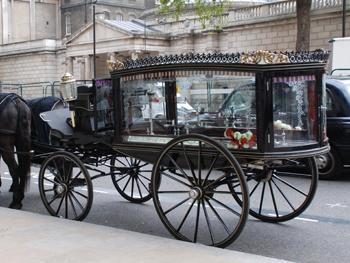 picture showing the splendid victorian glass sided hearse complete with black plumed horses and undertakers in big coats