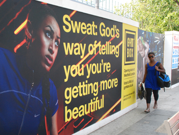 picture showing the poster for a new gym saying, sweat is god's way of telling you youre getting more beautiful