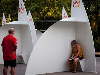 Photo of open-air confessional boxes in use